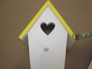 Paint each side of the birdhouse in the same colors you used on the birds.