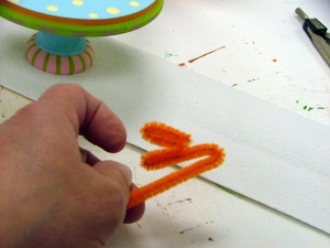Bend chenille into feet.