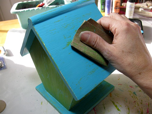 Use sandpaper to distress the bird house.