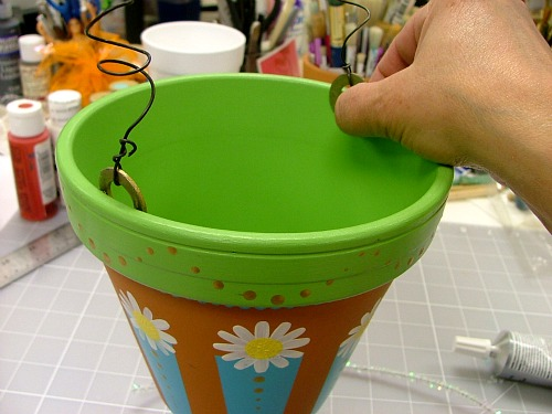 Glue washers to the inside edge of the pot to create the handle.