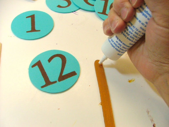 Place glue on sticks and attach numbers.