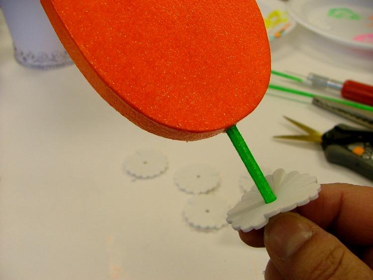 Glue flowers onto dowels and slide foam shapes onto the dowels.